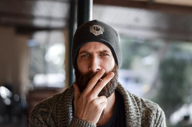 Homme barbu posant avec une cigarette.