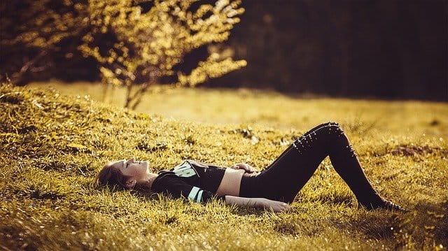 Jeune fille habillée en noir allongée sur l'herbe.