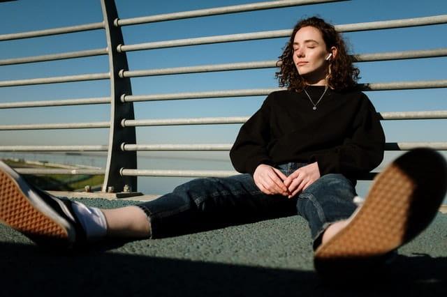 Femme en jean et baskets affalée par terre.